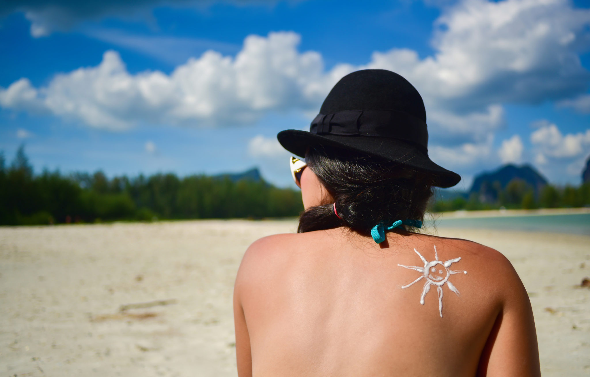 Asian woman traveler using skincare sunblock cream for sun protection in summer travel beach lifestyle